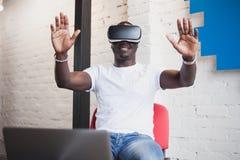 Νεαρός άνδρας που φορά τα γυαλιά εικονικής πραγματικότητας στο σύγχρονο εσωτερικό coworking στούντιο σχεδίου Smartphone χρησιμοπο Στοκ φωτογραφίες με δικαίωμα ελεύθερης χρήσης