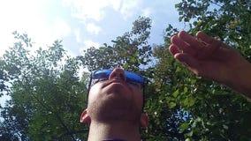 Νεαρός άνδρας που φορά τα μπλε γυαλιά ηλίου, κατώτατη άποψη απόθεμα βίντεο
