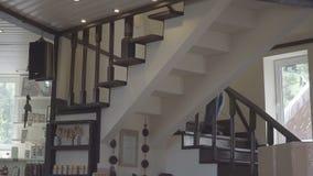 Νεαρός άνδρας που φορά τα τζιν που περπατούν κάτω από τα σκαλοπάτια στο σπίτι απόθεμα βίντεο
