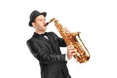 Νεαρός άνδρας που φορά το καπέλο και που παίζει στο saxophone Στοκ Εικόνες