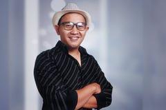 Νεαρός άνδρας που φορά το καπέλο της Αβάνας που χαμογελά με τα όπλα που διασχίζονται Στοκ Εικόνες