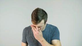 Νεαρός άνδρας που φτερνίζεται σε ένα άσπρο υπόβαθρο, σε αργή κίνηση Στοκ Εικόνες
