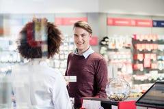 Νεαρός άνδρας που χαμογελά αγοράζοντας ένα χρήσιμο φαρμακευτικό προϊόν στοκ εικόνα με δικαίωμα ελεύθερης χρήσης