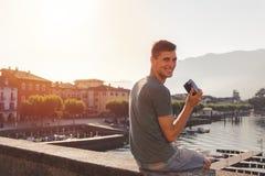 Νεαρός άνδρας που χρησιμοποιεί μια εκλεκτής ποιότητας κάμερα μπροστά από τον περίπατο λιμνών σε Ascona στοκ εικόνες