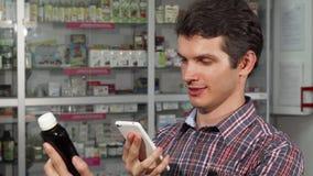 Νεαρός άνδρας που χρησιμοποιεί το έξυπνο τηλέφωνο ψωνίζοντας στο φαρμακείο απόθεμα βίντεο