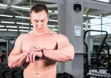 Νεαρός άνδρας που χρησιμοποιεί το βραχιόλι ικανότητας κατά τη διάρκεια του αθλητισμού που εκπαιδεύει στη γυμναστική Στοκ Εικόνα