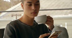 Νεαρός άνδρας που χρησιμοποιεί το κινητό τηλέφωνο ενώ έχοντας τον καφέ στο σπίτι 4k φιλμ μικρού μήκους