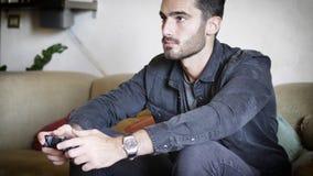 Νεαρός άνδρας που χρησιμοποιεί το πηδάλιο ή joypad για videogames Στοκ Φωτογραφία