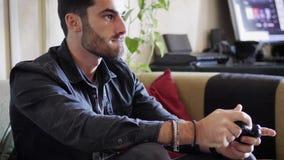 Νεαρός άνδρας που χρησιμοποιεί το πηδάλιο ή joypad για videogames Στοκ Εικόνα