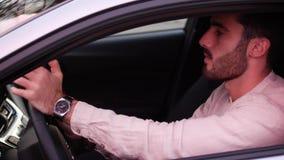 Νεαρός άνδρας που χρησιμοποιεί το τηλέφωνο κυττάρων του που ένα αυτοκίνητο απόθεμα βίντεο