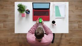 Νεαρός άνδρας που χρησιμοποιεί το τηλέφωνο με το κλειδί χρώματος, topshot, καθμένος πίσω από το γραφείο με το lap-top και τον καφ φιλμ μικρού μήκους
