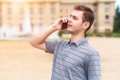 Νεαρός άνδρας που χρησιμοποιεί το τηλέφωνό του Στοκ Φωτογραφία
