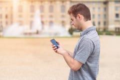 Νεαρός άνδρας που χρησιμοποιεί το τηλέφωνό του Στοκ εικόνες με δικαίωμα ελεύθερης χρήσης