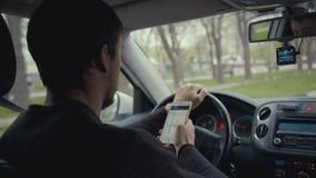 Νεαρός άνδρας που χρησιμοποιεί το χάρτη app στο smartphone του σε ένα αυτοκίνητο Στοκ Εικόνες
