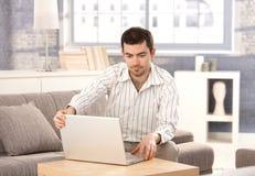 Νεαρός άνδρας που χρησιμοποιεί το lap-top που κάθεται στο σπίτι στον καναπέ Στοκ φωτογραφία με δικαίωμα ελεύθερης χρήσης