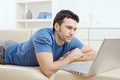 Νεαρός άνδρας που χρησιμοποιεί το lap-top στο σπίτι Στοκ φωτογραφία με δικαίωμα ελεύθερης χρήσης