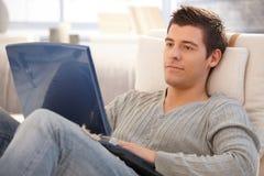 Νεαρός άνδρας που χρησιμοποιεί το lap-top στο σπίτι Στοκ Φωτογραφία