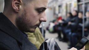 Νεαρός άνδρας που χρησιμοποιεί το smartphone κατά τη διάρκεια του γύρου μετρό απόθεμα βίντεο