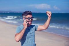 Νεαρός άνδρας που χρησιμοποιεί το smartphone στην παραλία Στοκ Εικόνα