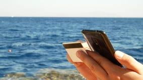 Νεαρός άνδρας που ψωνίζει on-line με την πιστωτική κάρτα και το smartphone απόθεμα βίντεο