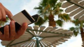 Νεαρός άνδρας που ψωνίζει on-line με την πιστωτική κάρτα και το smartphone φιλμ μικρού μήκους