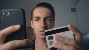 Νεαρός άνδρας που ψωνίζει on-line με την πιστωτική κάρτα που χρησιμοποιεί το smartphone στο σπίτι Σε απευθείας σύνδεση τραπεζικές απόθεμα βίντεο