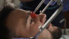 Νεαρός άνδρας σε έναν διορισμό οδοντιάτρων ` s Εγκατάσταση του πρόσωπο-τόξου απόθεμα βίντεο