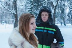 Νεαρός άνδρας σε ένα καπέλο γουνών με ένα earflap και ένα κορίτσι σε ένα μπεζ παλτό γουνών στα πλαίσια του χειμερινού δάσους στοκ φωτογραφίες με δικαίωμα ελεύθερης χρήσης