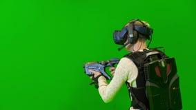 Νεαρός άνδρας σε ένα κράνος VR στους στόχους κάλυψης από ένα πυροβόλο όπλο φιλμ μικρού μήκους