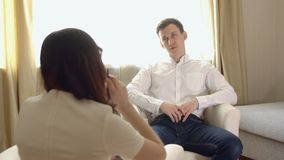 Νεαρός άνδρας σε μια υποδοχή με έναν θηλυκό ψυχολόγο απόθεμα βίντεο