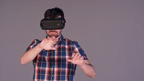 Νεαρός άνδρας στα γυαλιά εικονικής πραγματικότητας σχετικά με μια φανταστική οθόνη Στοκ Εικόνα