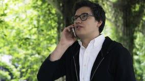 Νεαρός άνδρας στα γυαλιά που απολαμβάνει έναν περίπατο σε ένα πάρκο και μια τηλεφωνική συνομιλία απόθεμα βίντεο
