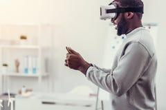 Νεαρός άνδρας στα περιστασιακά παίζοντας παιχνίδια εικονικής πραγματικότητας Στοκ Φωτογραφίες