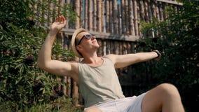 Νεαρός άνδρας στα σορτς, τη συνεδρίαση χορού μπλουζών και καπέλων έξω απόθεμα βίντεο