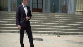 Νεαρός άνδρας στην αναμονή κοστουμιών, που μένει και που θέτει σε μια πόλη απόθεμα βίντεο