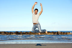 Νεαρός άνδρας στην περιστασιακή ένδυση που πηδά στον αέρα στην παραλία Στοκ Φωτογραφίες