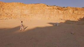 Νεαρός άνδρας στις εθνικές ξυπόλυτες προσεγγίσεις ενδυμάτων το άσπρο πιάνο ενάντια στο σκηνικό ενός λατομείου άμμου εναέρια όψη φιλμ μικρού μήκους
