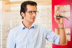 Νεαρός άνδρας στον οπτικό με τα γυαλιά Στοκ Φωτογραφία