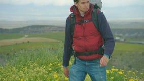 Νεαρός άνδρας στον υπαίθριο ιματισμό με τον εξοπλισμό ταξιδιού που, τουρισμός, αναψυχή απόθεμα βίντεο