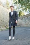 Νεαρός άνδρας στο γκρίζο παλτό, άσπρο πουκάμισο, βέβαιο, επιτυχία στοκ φωτογραφίες