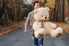 Νεαρός άνδρας στο δρόμο πάρκων φθινοπώρου με το μεγάλο παιχνίδι αρκούδων στοκ εικόνες