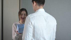 Νεαρός άνδρας στο δόσιμο του κιβωτίου δώρων βαλεντίνων στη φίλη του απόθεμα βίντεο