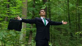 Νεαρός άνδρας στο επιχειρησιακό κοστούμι που αναπνέει βαθιά υπαίθρια, που αφαιρεί από την πίεση πόλεων απόθεμα βίντεο