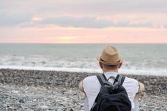Νεαρός άνδρας στο καπέλο και με τη συνεδρίαση σακιδίων πλάτης στην παραλία Θάλασσα και Στοκ Εικόνες