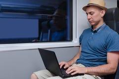 Νεαρός άνδρας στο καπέλο που λειτουργεί πίσω από μια συνεδρίαση lap-top σε ένα chai τραίνων Στοκ φωτογραφία με δικαίωμα ελεύθερης χρήσης