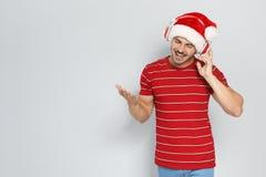 Νεαρός άνδρας στο καπέλο Santa που ακούει τη μουσική Χριστουγέννων Στοκ Εικόνα