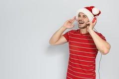 Νεαρός άνδρας στο καπέλο Santa που ακούει τη μουσική Χριστουγέννων Στοκ φωτογραφίες με δικαίωμα ελεύθερης χρήσης