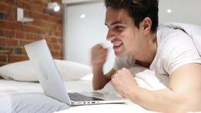 Νεαρός άνδρας στο κρεβάτι που λειτουργεί στο lap-top και που αντιδρά στην επιτυχία φιλμ μικρού μήκους