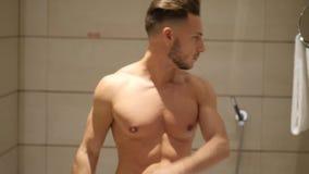 Νεαρός άνδρας στο λουτρό, την ψεκάζοντας Κολωνία ή το άρωμα απόθεμα βίντεο