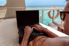 Νεαρός άνδρας στο μαγιό που λειτουργεί σε έναν υπολογιστή σε μια καρέκλα ινδικού καλάμου Σαφές μπλε τροπικό νερό ως υπόβαθρο στοκ εικόνα με δικαίωμα ελεύθερης χρήσης